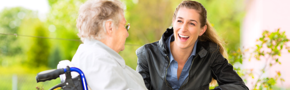 caregiver wearing black jacket and patient smiling at each other